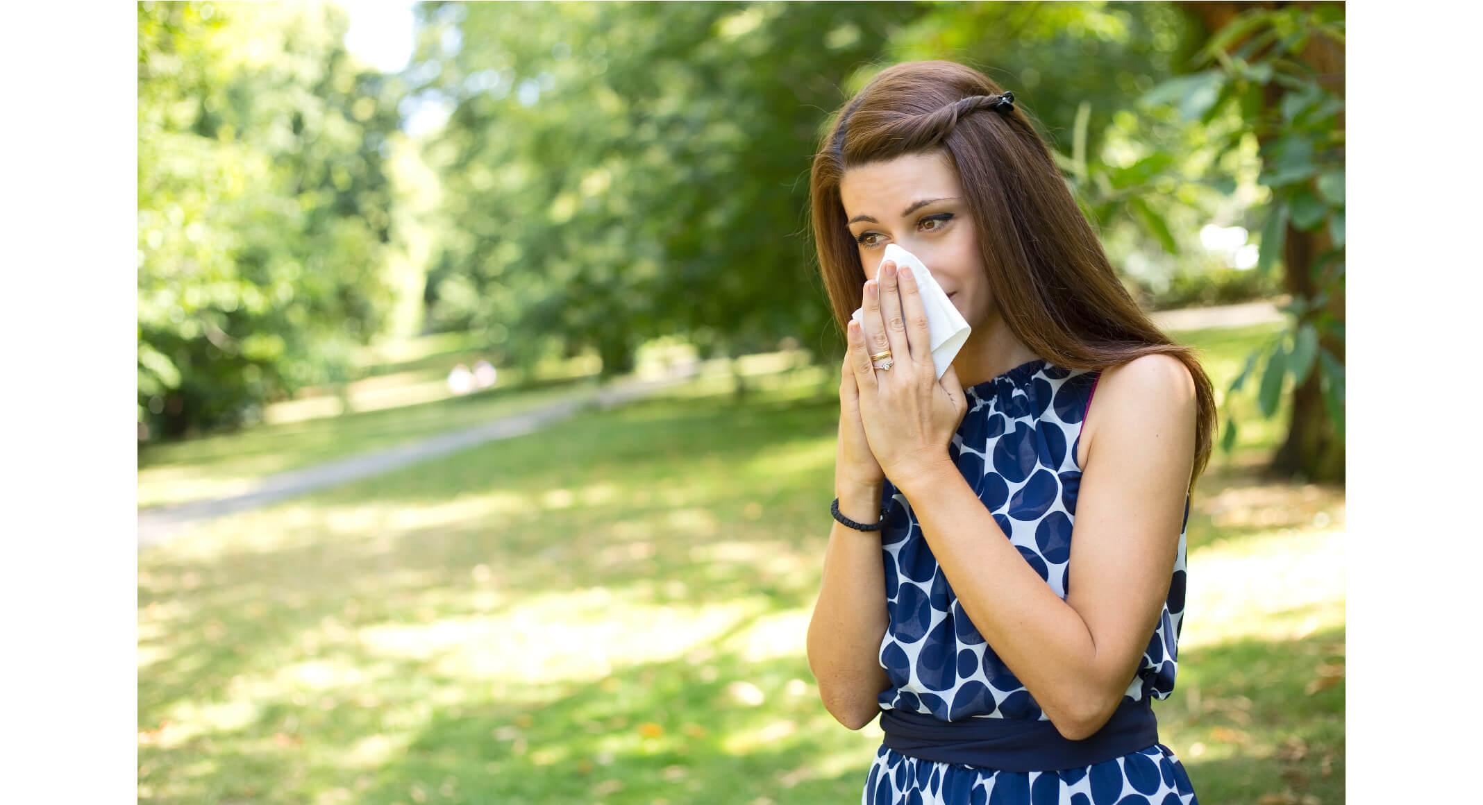 Frau putzt sich die Nase im Sommer, Sommergrippe-natürlich-behandeln